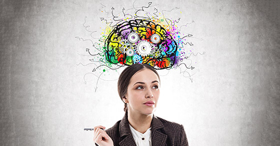 Pensive young businesswoman wearing a suit is holding a pen and thinking. A concrete wall background with a cog brain sketch on it.