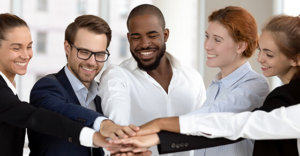 5 people putting their hands together in the center to symbolize teamwork