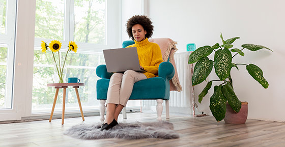 individual sitting in a chair next to a window. individual is in a casual outfit wiht a laptop on her lap and plants on either side of her.