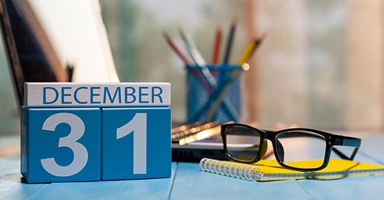 desk with a calendar sitting on top and the page December 31 is showing.