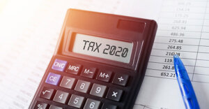 calculator on top of papers. The calculator reads: Tax 2020