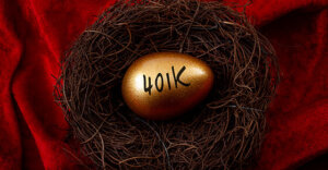 "Golden colored egg with ""401K"" on it. The nest is on a red tablecloth."