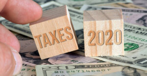 "two blocks on top of money. the first block has the text ""taxes"" and the second block has the text ""2020"""