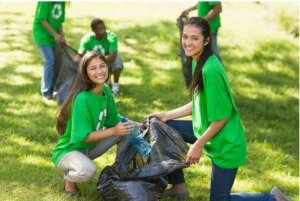 Two volunteers putting trash into a bag