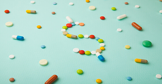 pills on a table forming the $ symbol.