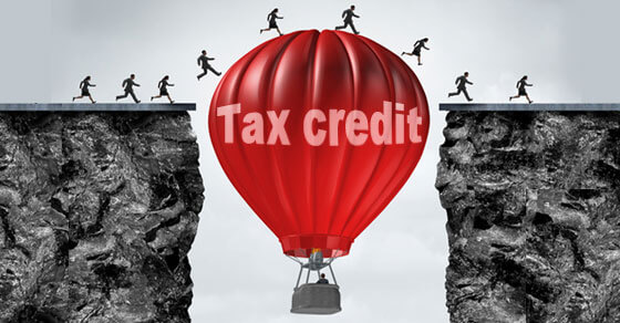 "image of people walking on a hot air balloon that is placed in the middle of two cliffs. the red hot air balloon has ""tax credit"" written on it."