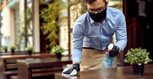 employee wiping down a table in a restaurant wearing gloves and a mask.