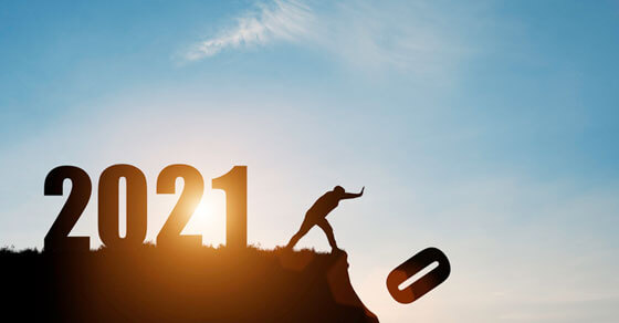 """on the top of a hill are the number 2021 with an individual seemingly pushing """"0"""" off the cliff. The depiction is that 2020 is being replaced by 2021"""