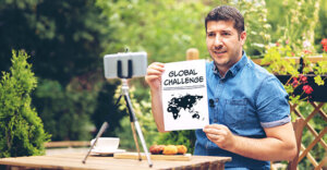 """man holding a book with the title """"Global Challenge"""" as he talks to someone via his phone on video."""