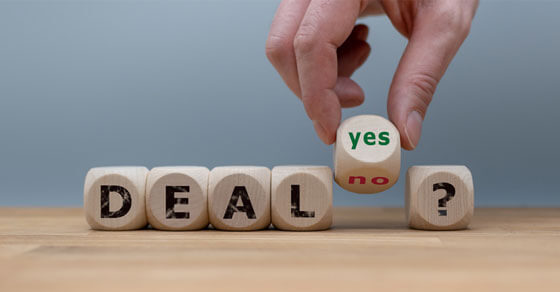 """scrabble tiles spelling out """"DEAL?"""" with a yes/no dice before the question mark."""