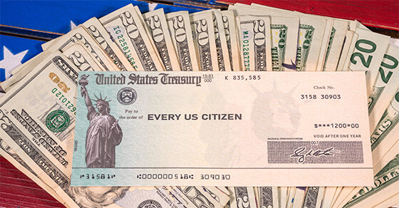 """$20 bills spreadout on a table with a government issued check on top for the amount of $1,400 directed to """"every US citizen"""""""
