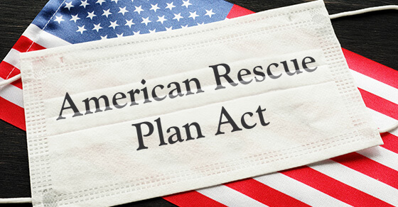 "disposable mask on top of the american flag. the mask has the words ""American Rescue Plan Act"""