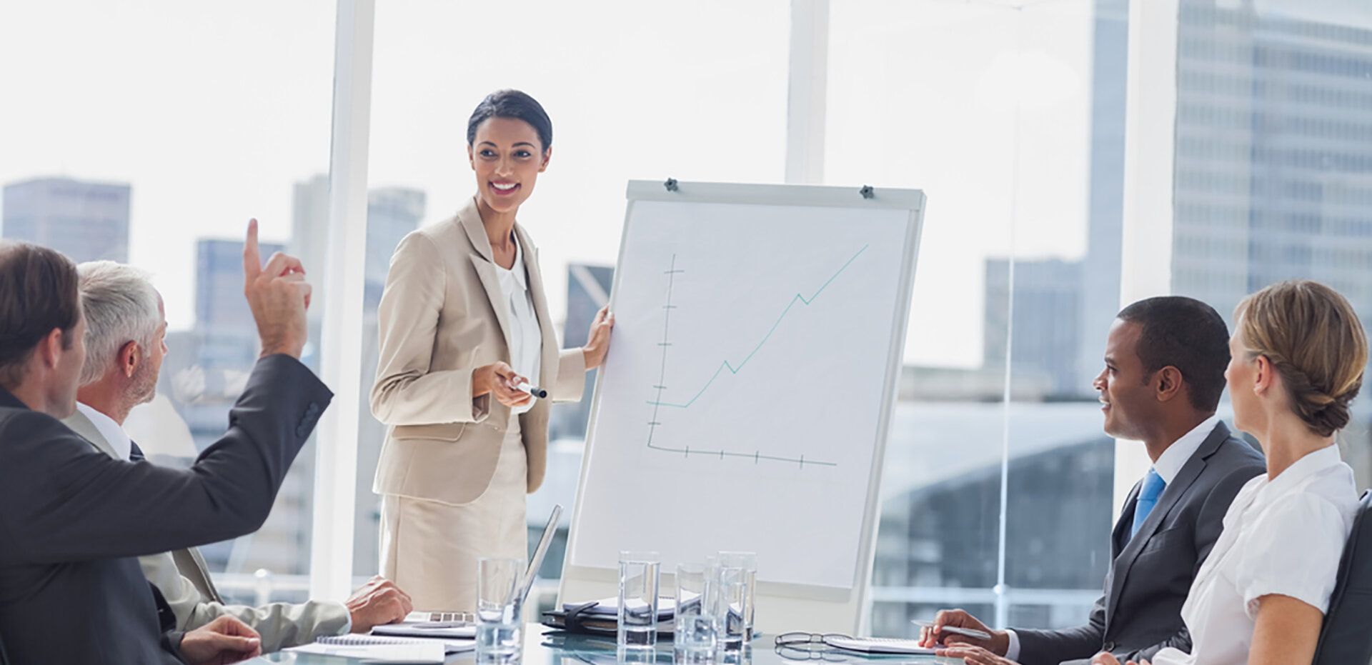 image of people in a boardroom, dressed in professional attire, looking at someone standing at the head of the table with a whiteboard drawing a graph.