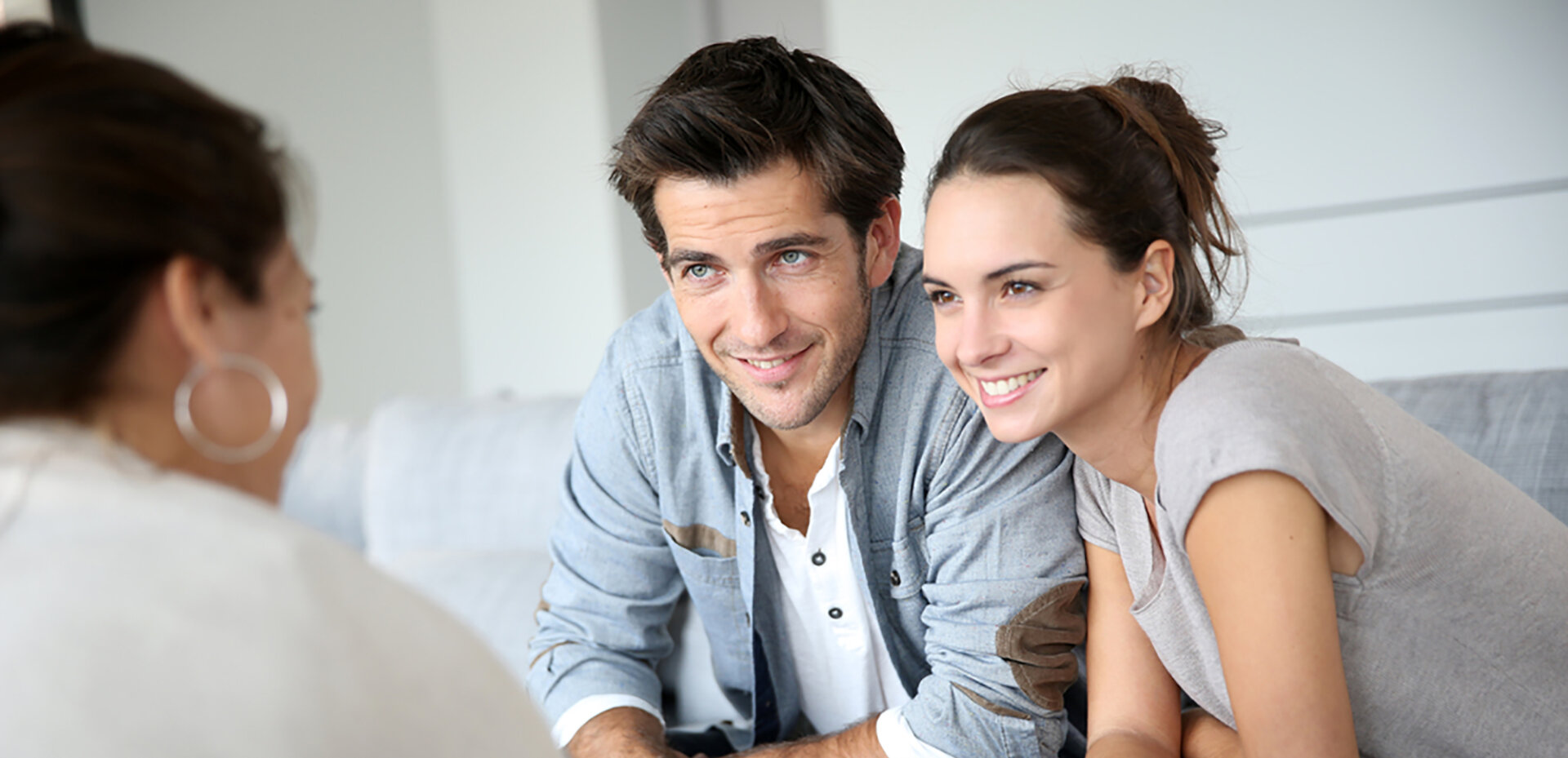 Couple smiling as financial advisor shows them the tax credits and deductions available.