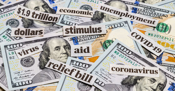 """image of money on a table and words cut out of paper, placed on top of the month. Words include """"stimulus"""", """"relief bill"""", """"economic"""", """"unemployment"""""""