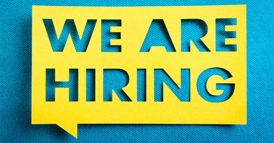 """yellow stencil with the words """"we are hiring"""" cut out and placed on top of a blue print"""
