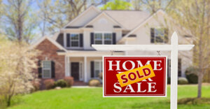 """image of a house with a """"sold"""" sign posted in front."""