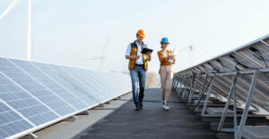 two people walking in between solar panels on a roof. They are wearing construction hats.