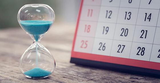 hourglass with blue sand and a desktop calendar