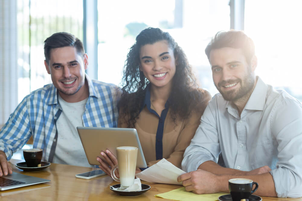 Portrait of smiling friends using digital tablet and laptop in cafe