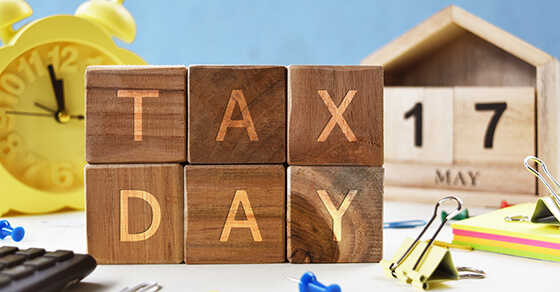 """table with block letters spelling out """"Tax Day"""" on it. Behind the blocks is a clock and a calendar with the date May 17"""