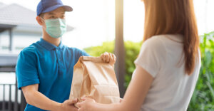 delivery person handing a bag to someone else. Delivery person has a mask on.