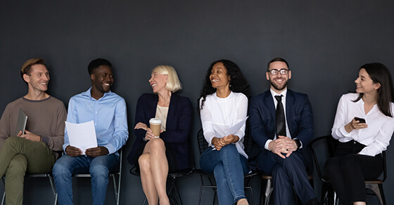 A row of people sitting and smiling.