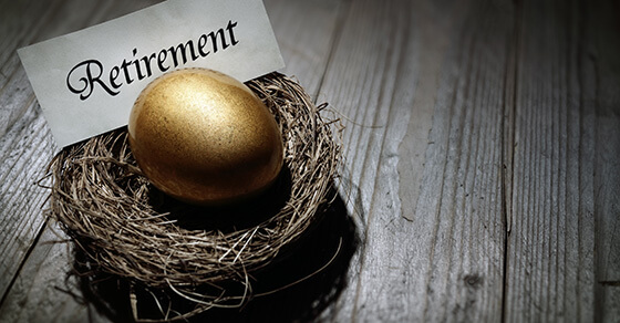 """a golden egg in a nest sitting on a table with the sign """"retirement"""" next to the egg."""