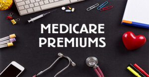 """the text """"Medicare Premiums"""" is written above a table with a computer, a stethoscope, paper clips, and other medical office supplies."""