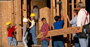 young school age children, with construction hats on, assisting in building a house.