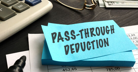 """a blue post-it note with """"Pass-through deduction"""" written in black ink, on a desk with a calculator, stapler remover, paper clip and other office supplies."""