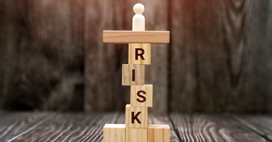 """""""risk"""" spelled out on jenga blocks stacked on top of each other on a table"""