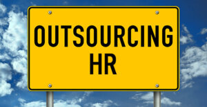 """yellow traffic sign with """"Outsourcing HR"""" written in black letters."""