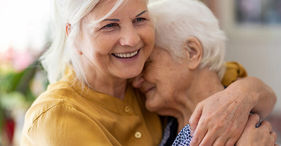 a younger woman hugging an older woman