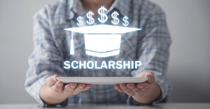 """individual holding a piece of paper with a graphic of a graduation cap and money symbols with the word """"scholarship""""."""