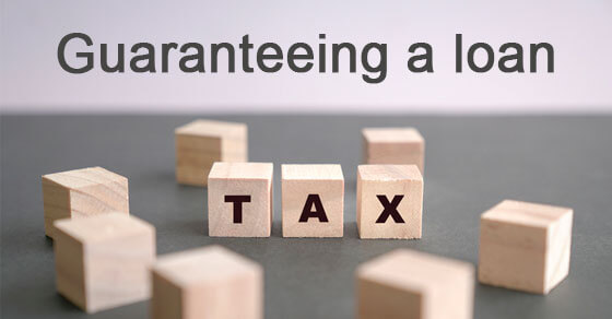 """scrabble boxes on a board spelling """"tax"""" with the words 'guaranteeing a loan"""" above it."""