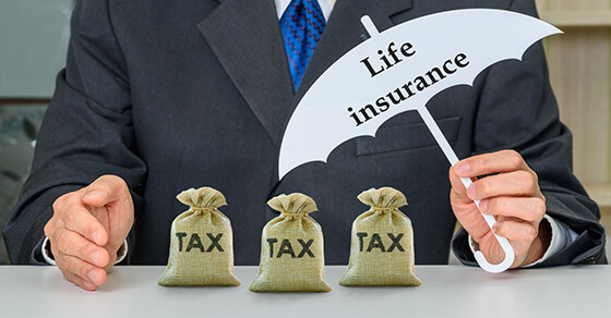 """An individual holding an umbrella over three little bags of money. The umbrella says """"Life Insurance"""""""