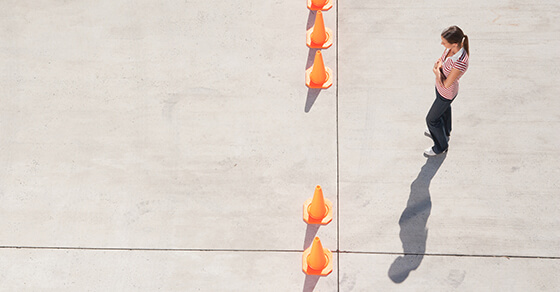 individual standing behind several cones in a line and there is a gap in the middle.