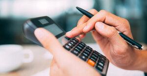 closeup of a person typing into a calculator