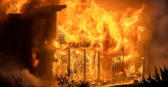 image of an actively burning building with billows of orange and red fire.