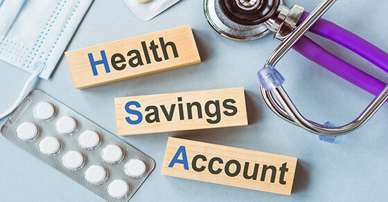 """Three blocks with words on them are in the picture """"Health"""", """"Savings"""", """"Account"""". On either side of the blocks are medical tools such as pills and a stethoscope."""