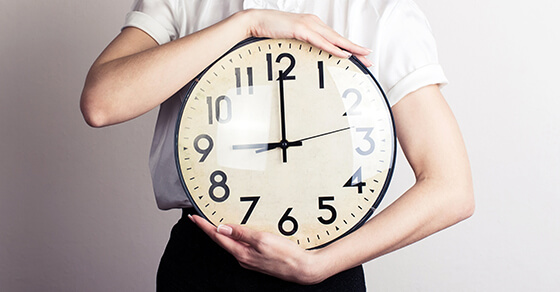 image of someone holding a large clock.