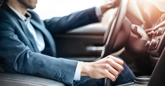 image of a person in a business suite driving a car.