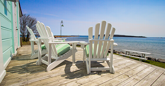 beach chairs on a deck placed facing the ocean with a lighthouse in the distance.